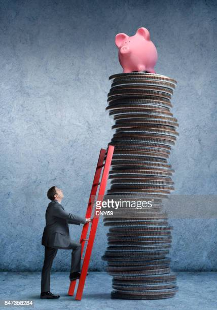 Businessman Climbing Stack Of Coins With Piggy Bank At Top