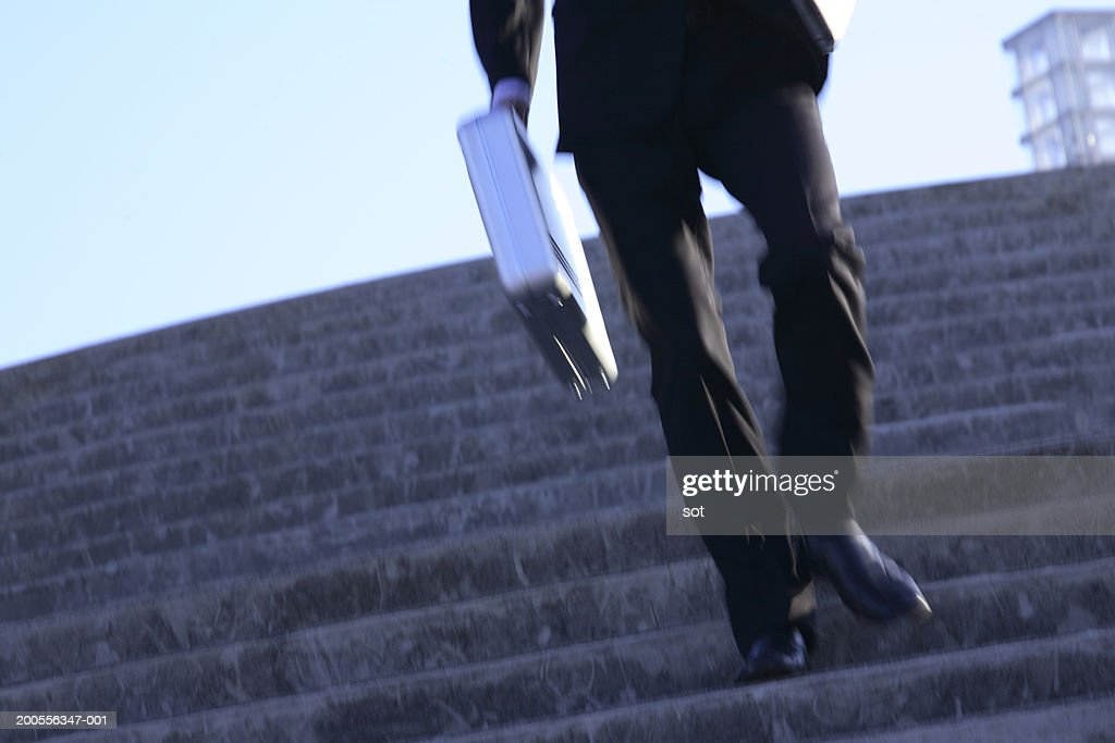 businessman climbing steps outdoors low section stock photo getty