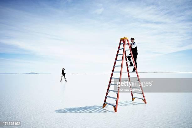 Businessman climbing tall ladder in lake