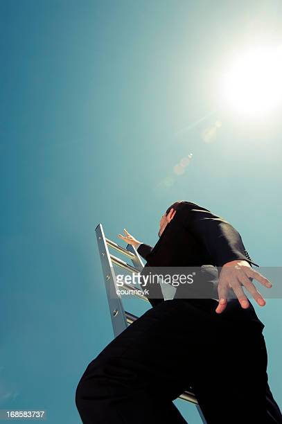 businessman climbing the ladder of success - metallic suit stock photos and pictures