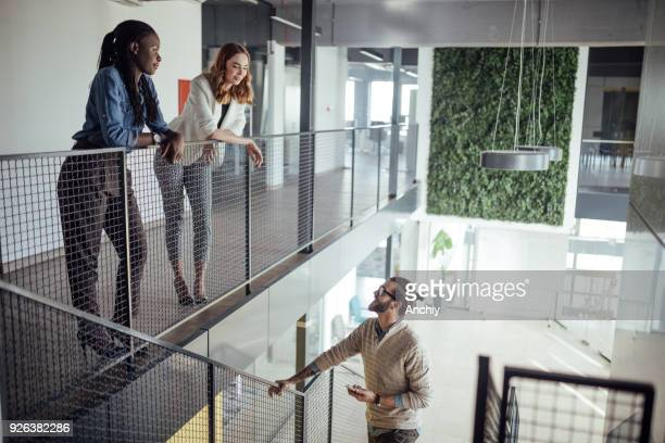 Businessman climbing the stairs and talking to his female coworkers