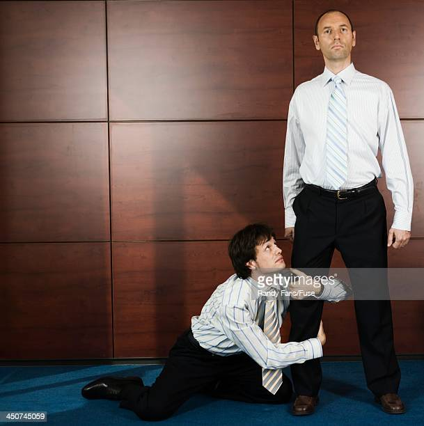 Businessman Clinging to Supervisor's Leg