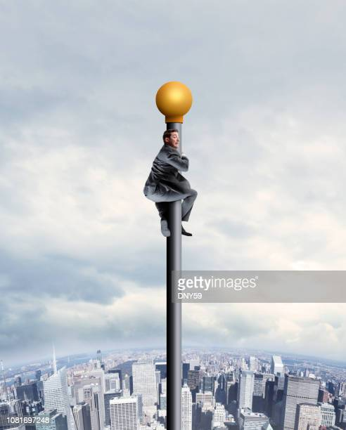 businessman clings to a tall flagpole above urban skyline - pole stock pictures, royalty-free photos & images