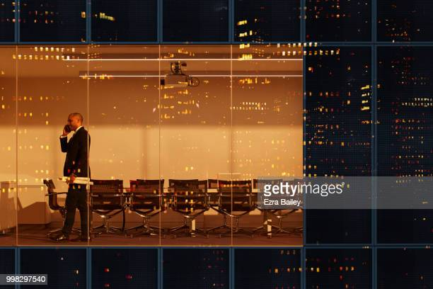 Businessman closing a deal in the boardroom of a modern high rise office at night.