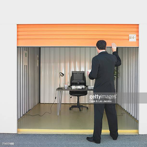 businessman closing door of storage unit office - roller shutter stock pictures, royalty-free photos & images