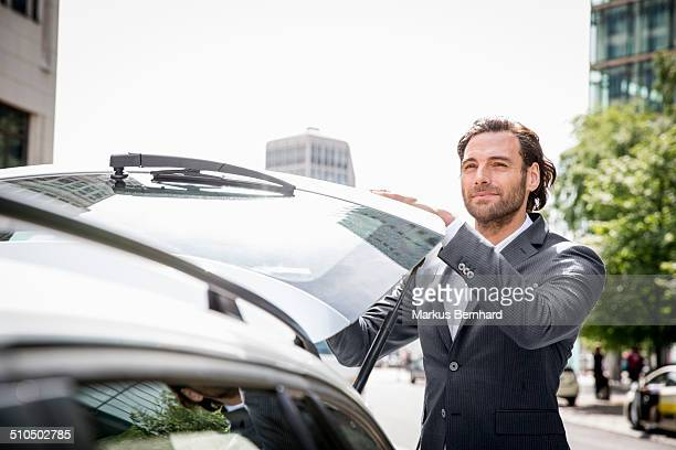 businessman closing trunk of his car. - closing stock photos and pictures