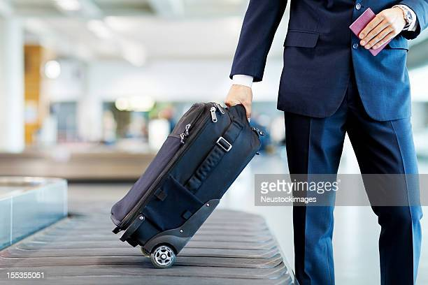 businessman collecting his luggage - baggage claim stock pictures, royalty-free photos & images