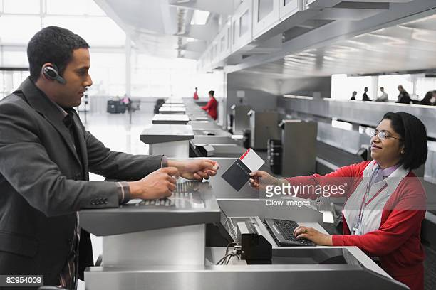Businessman collecting his passport with an airplane ticket from the airline check-in attendant