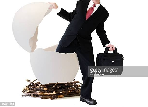 Businessman coming out of a giant egg shell in a large nest