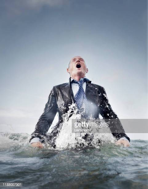 a businessman coming out of the sea - caucasian appearance stock pictures, royalty-free photos & images