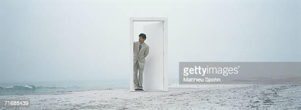 businessman coming through doorway on beach - doorway stock pictures, royalty-free photos & images