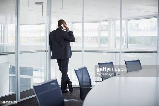businessman communicating on mobile phone - leaning stock pictures, royalty-free photos & images