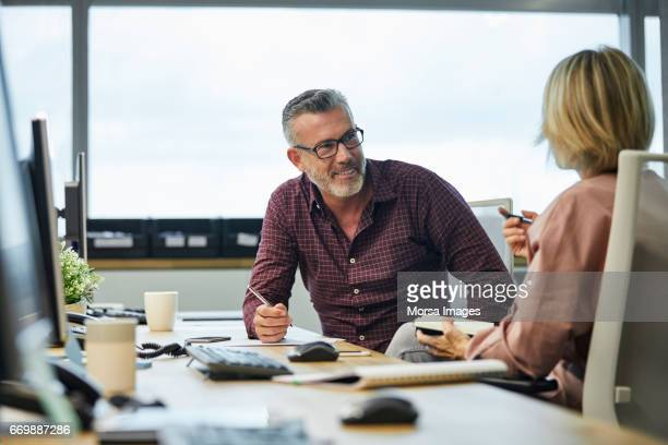 businessman communicating with colleague at desk - part of a series stock pictures, royalty-free photos & images