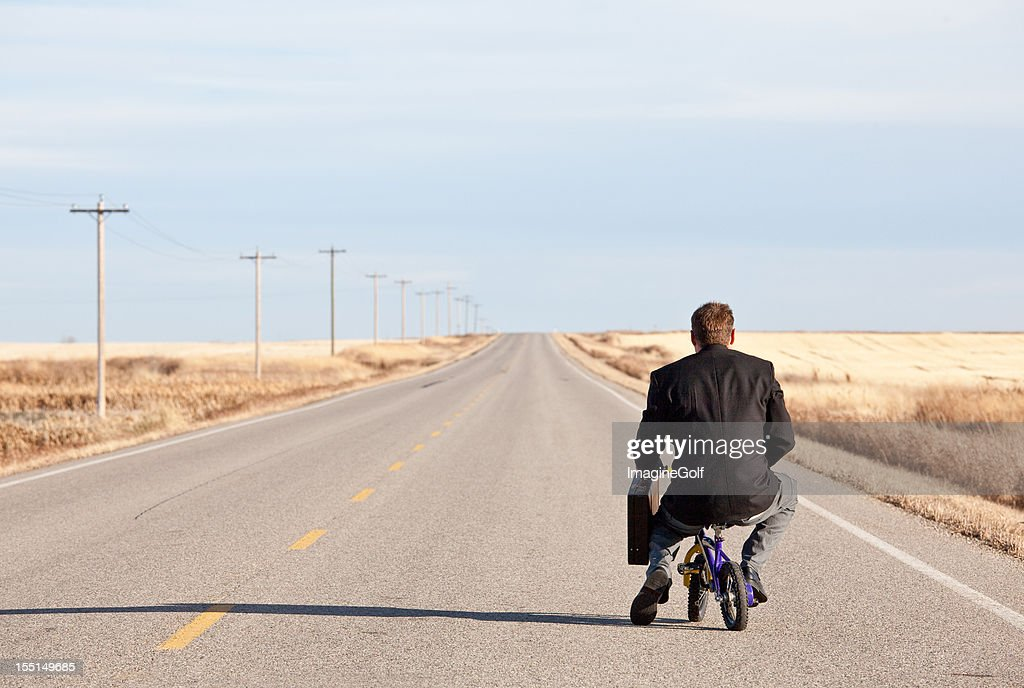 Businessman Commuting on Tiny Bicycle : Stock Photo