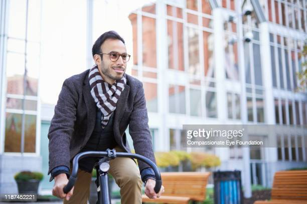 businessman commuting, riding bicycle on urban street - striped blazer stock pictures, royalty-free photos & images