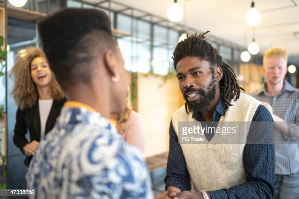 businessman congratulating speaker after seminar - dreadlocks stock pictures, royalty-free photos & images