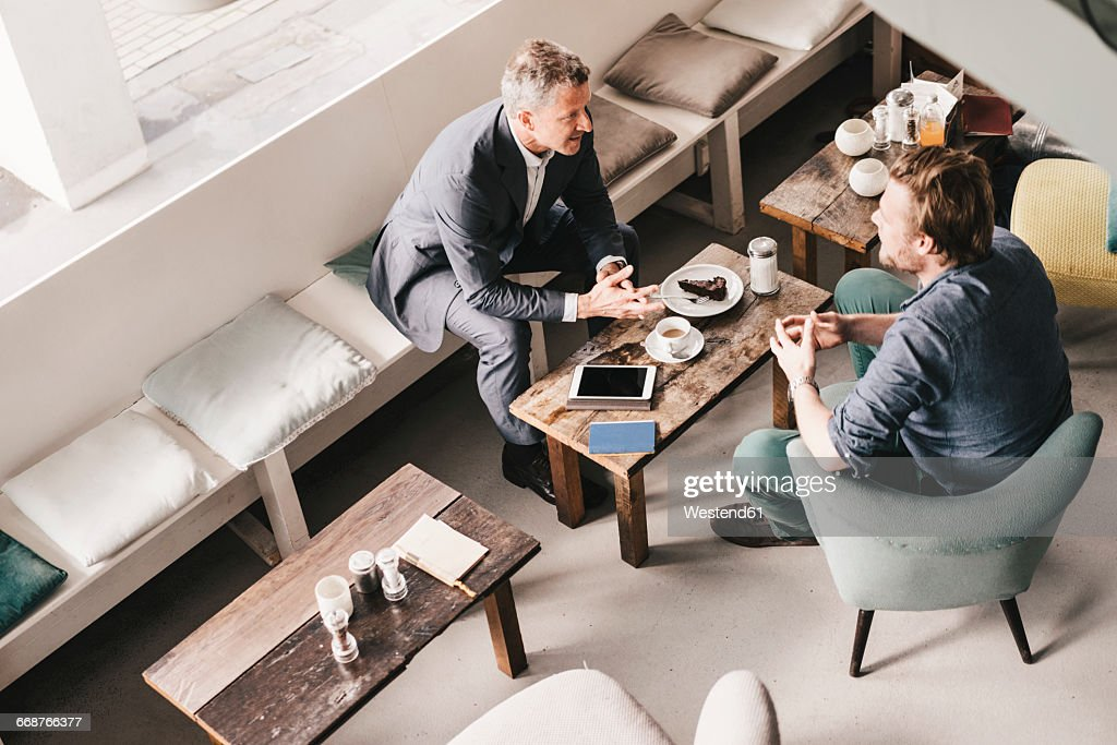 Businessman consulting customer in cafe : Stock Photo