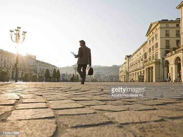businessman consults digital tablet,crosses piazza - torino foto e immagini stock