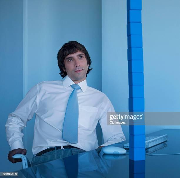 Businessman contemplating building blocks