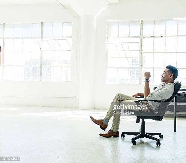 businessman contemplating by office window - office chair stock pictures, royalty-free photos & images