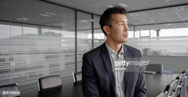 Businessman contemplating in empty conference room