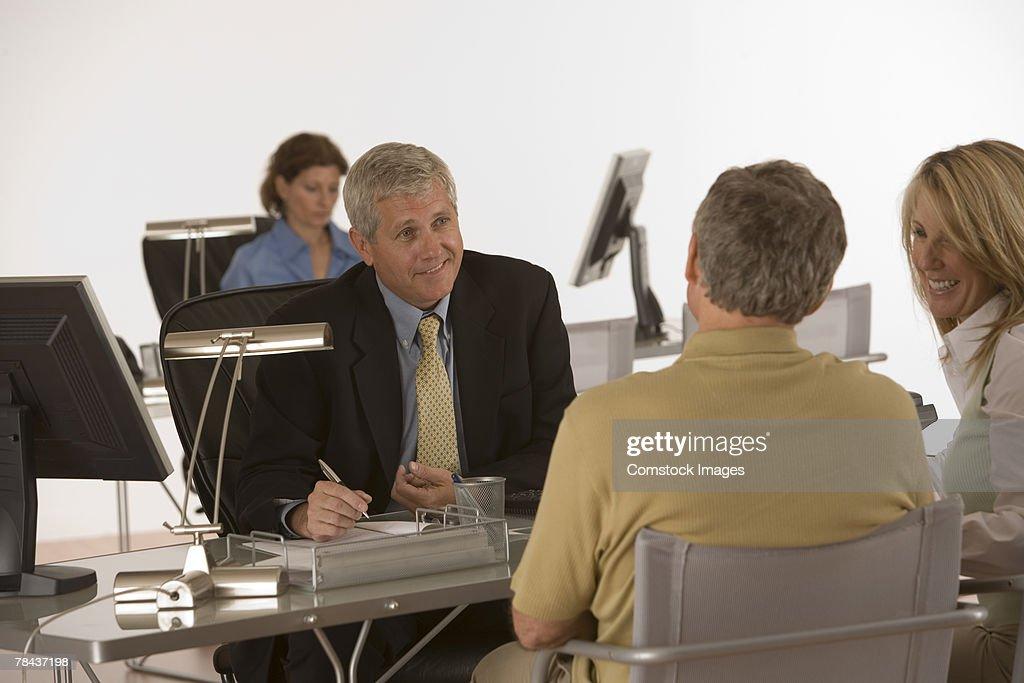 Businessman conversing with couple : Stockfoto