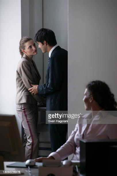 businessman cornering businesswoman at photocopier in office - taking a corner stock pictures, royalty-free photos & images