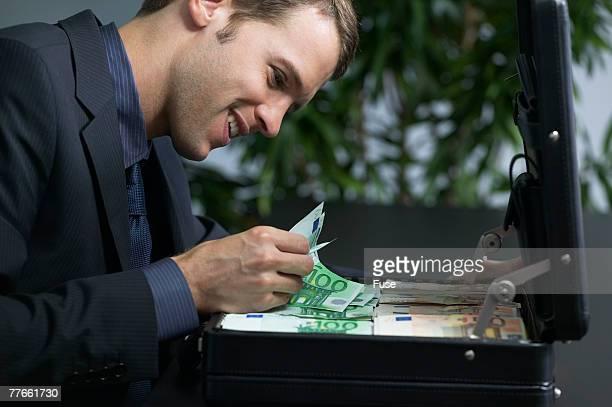 businessman counting money in briefcase - bestechung stock-fotos und bilder