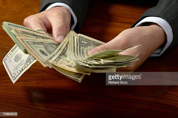 businessman counting money on desk, close up, close-up - richard drury stock pictures, royalty-free photos & images