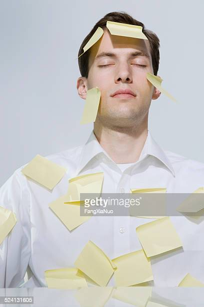 Businessman covered with adhesive notes, eyes closed