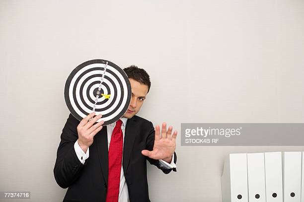 Businessman covering face with a dartboard