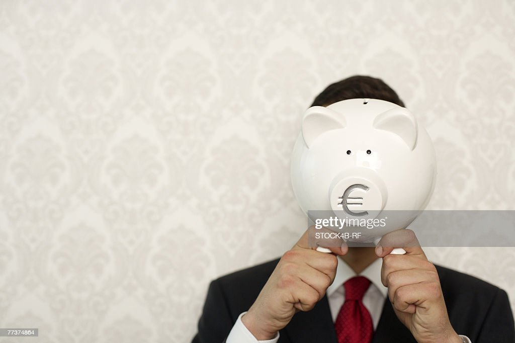Businessman covering face with a piggy bank : Stock Photo