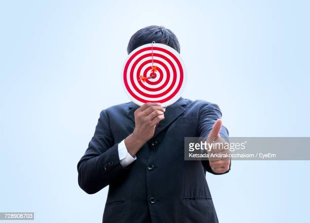 Businessman Covering Face With Dartboard Gesturing Thumbs Up Against White Background