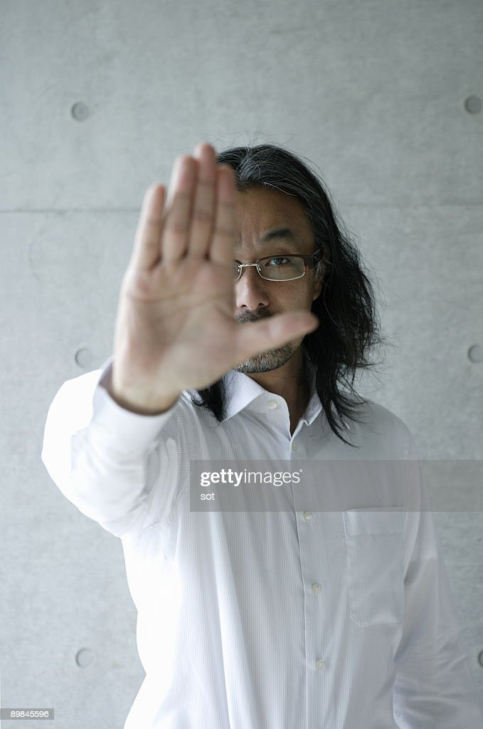 Businessman covering face with hand, close-up : Stock Photo