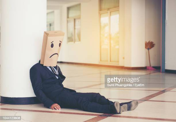 businessman covering face with paper bag while sitting on floor - aborto fotografías e imágenes de stock
