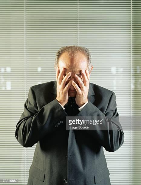 Homme d'affaires couvrant son visage avec ses mains