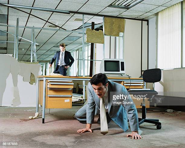 Businessman crawling away from attacking colleague