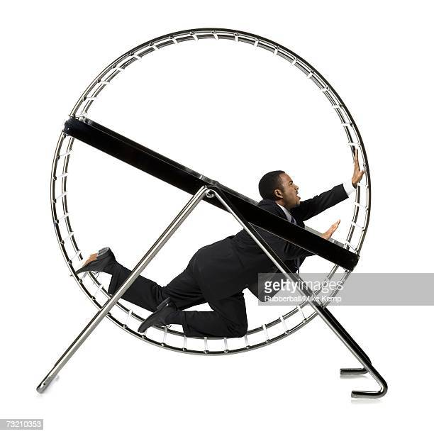 Businessman crawling in rodent wheel