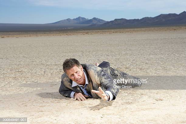 Businessman crawling on dry lake bed, reaching out