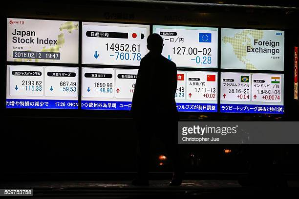 A businessman crosses the street looking at the stock market indicator board on February 12 2016 in Tokyo Japan The Nikkei Stock Average finished 11%...
