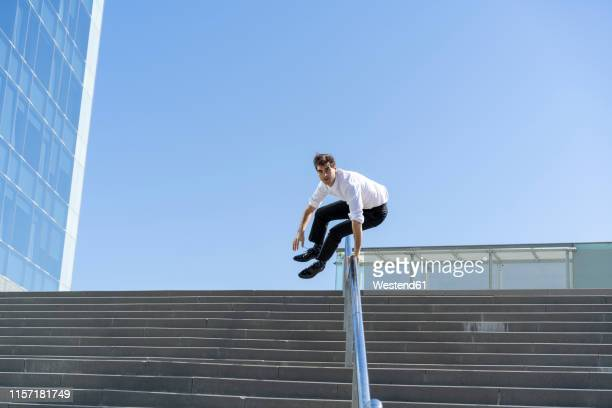 businessman crossing banister in the city - 軽い ストックフォトと画像