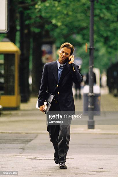 Businessman crossing city street talking on cell phone