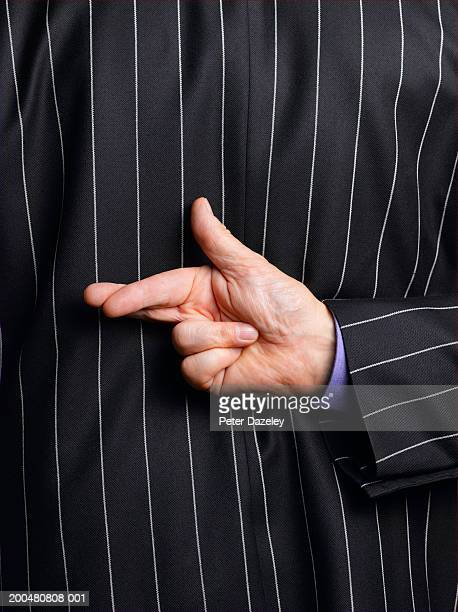 Businessman crossing fingers behind back, rear view, mid section