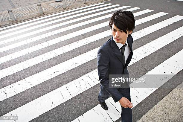 Businessman crossing road, looking away