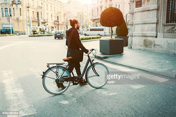 Businessman Crossing The Street With Bicycle.