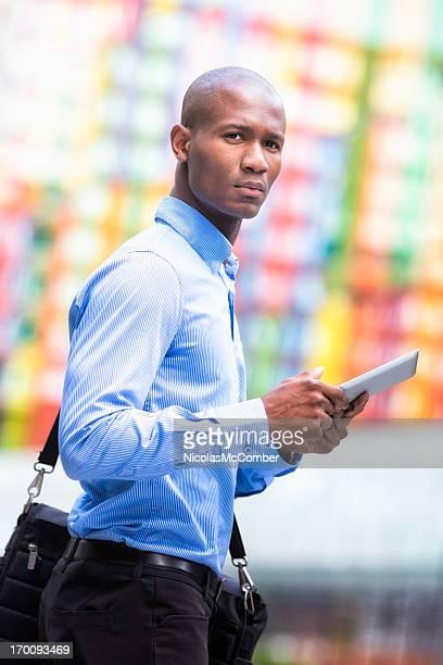 Homme d'affaires traversant la rue avec une tablette vertical