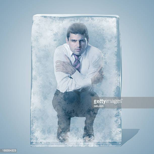 Businessman crouched frozen in an ice space
