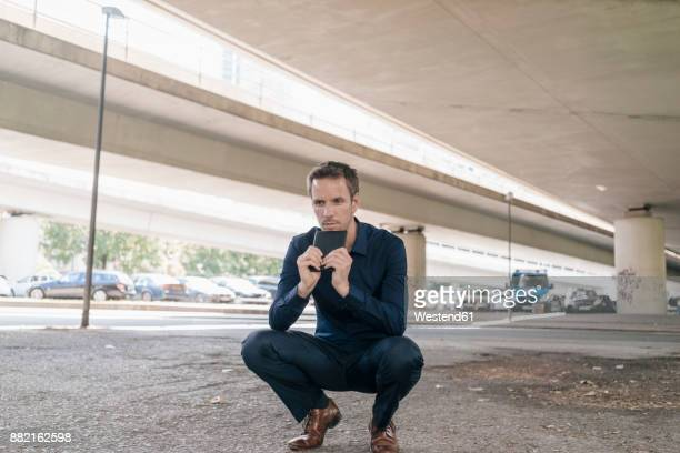 Businessman crouching at underpass holding tablet