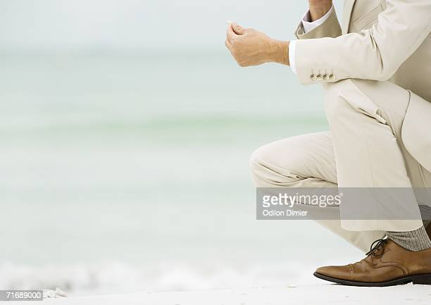 businessman crouching on beach, holding something in fingers - beige suit stock pictures, royalty-free photos & images
