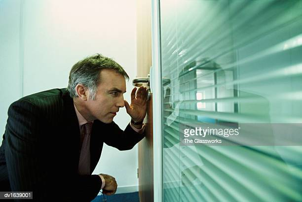 Businessman Crouching, Peeking Through the Keyhole of a Door in an Office
